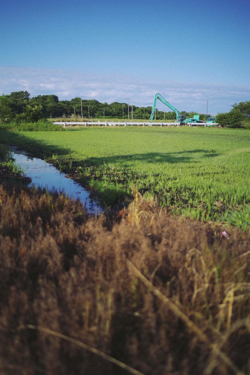 「工事中の重機と放置された畑」の写真