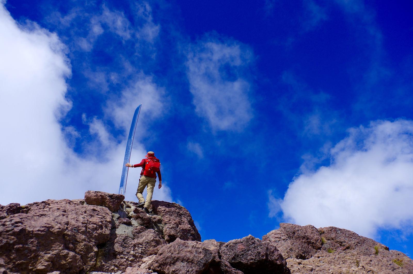「男体山の刀と赤い登山者」の写真