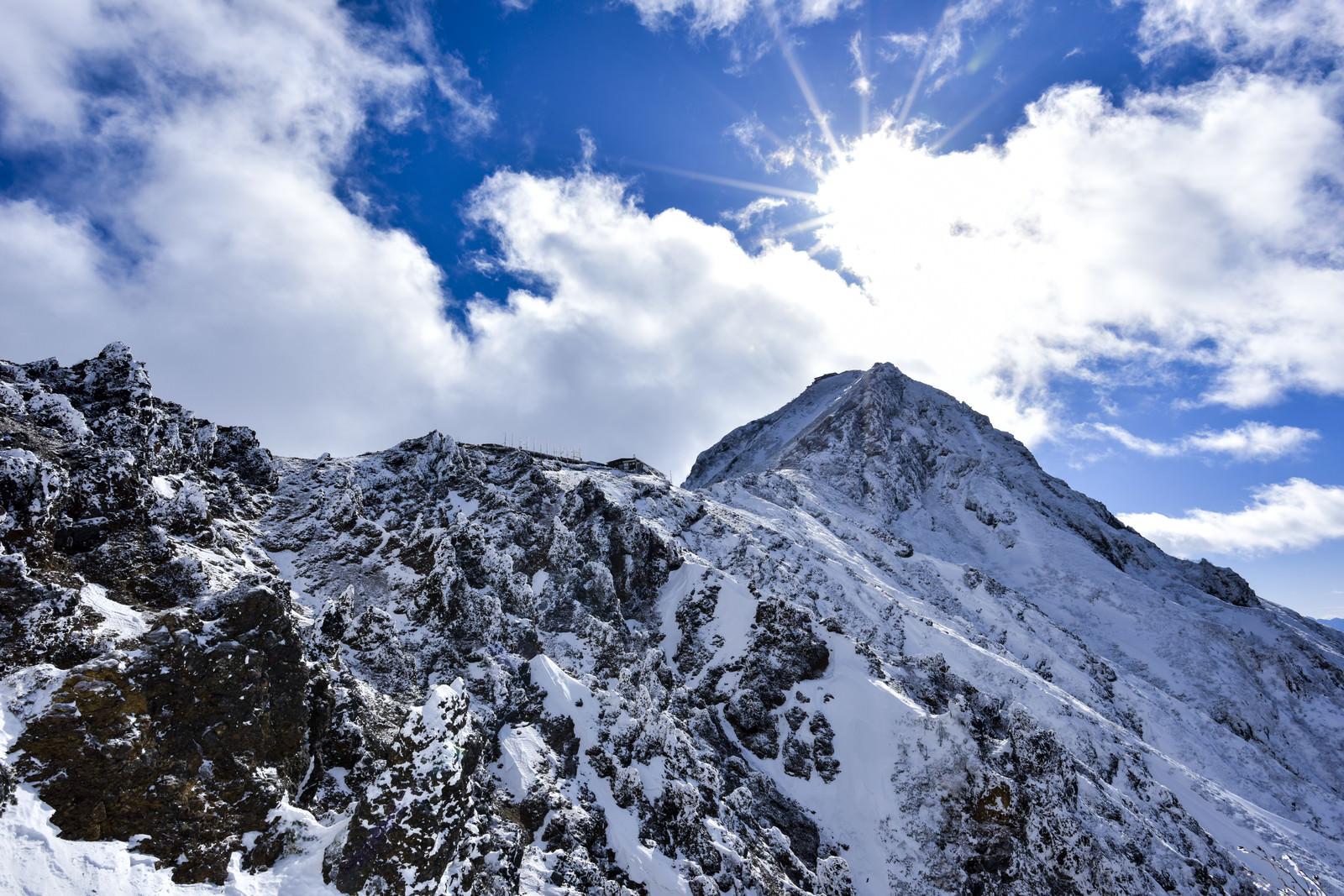 「冬の地蔵尾根稜線側から見る山荘と山頂」の写真
