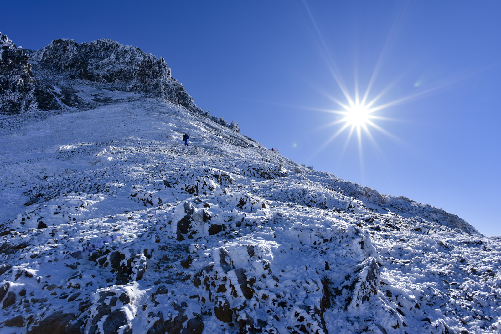 「冬の文三郎尾根を登る登山者とピーカンの太陽」の写真