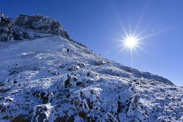 冬の文三郎尾根を登る登山者とピーカンの太陽の写真