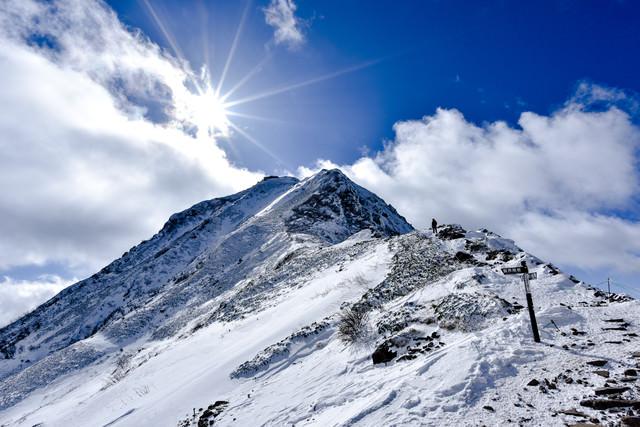 冬の赤岳山頂を照らす太陽の写真