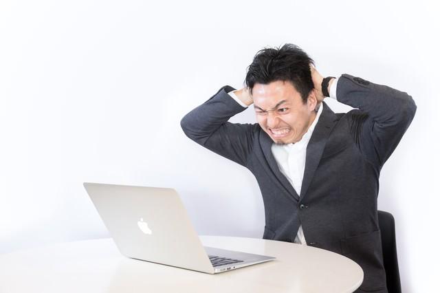 強制決済で頭を抱える男性の写真