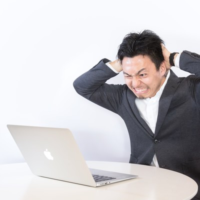 「強制決済で頭を抱える男性」の写真素材
