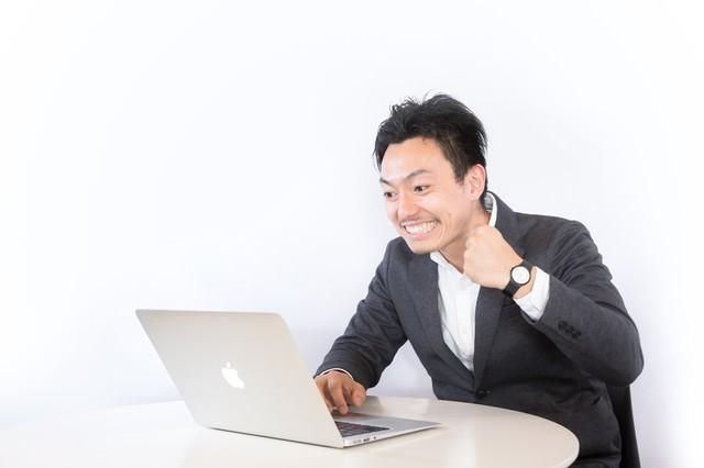 PC見ながらニヤニヤする男性の写真
