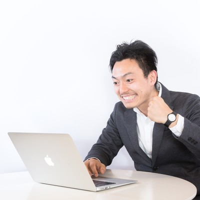 「PC見ながらニヤニヤする男性」の写真素材