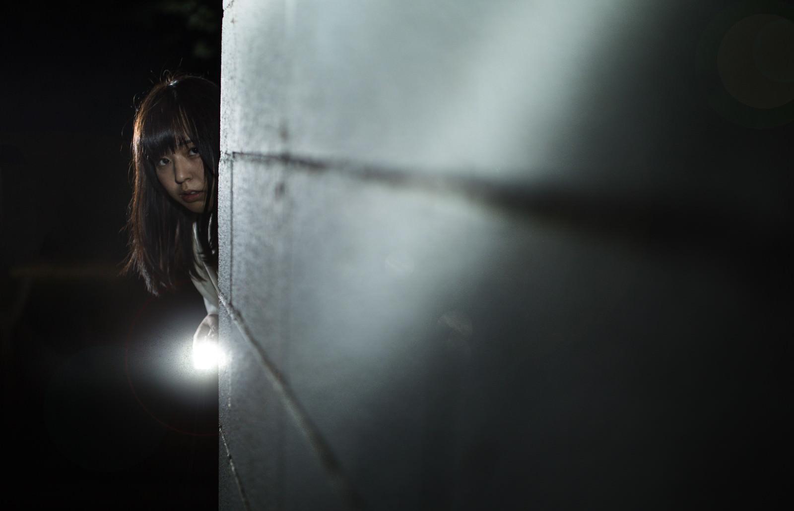 「ハンドライトで照らしながら恐る恐る前に進む女性」の写真[モデル:さとうゆい]