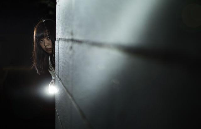ハンドライトで照らしながら恐る恐る前に進む女性の写真