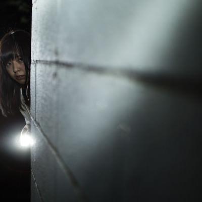 「ハンドライトで照らしながら恐る恐る前に進む女性」の写真素材