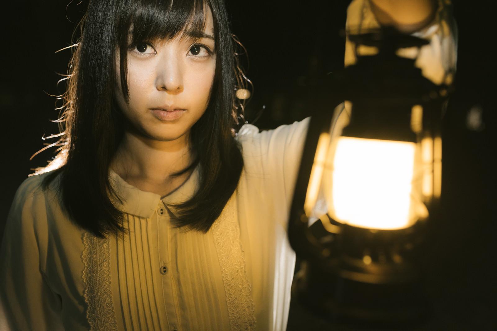 ランタンを使って辺りを照らす女性|ぱくたそフリー写真素材