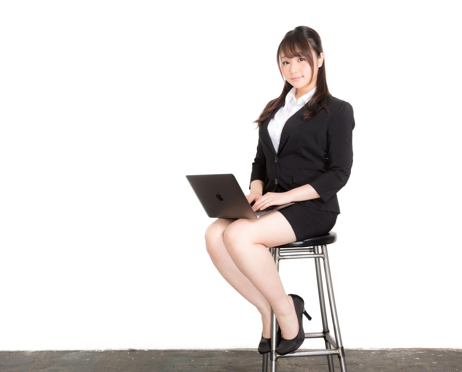 「椅子に座ってスライドを確認する新卒の女性」の写真[モデル:茜さや]