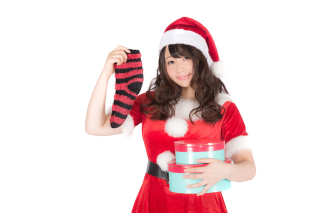 「靴下とプレゼントを持った女性サンタさん」のフリー写真素材