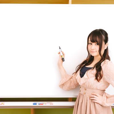 「ホワイトボードに書いて説明する美人広報」の写真素材