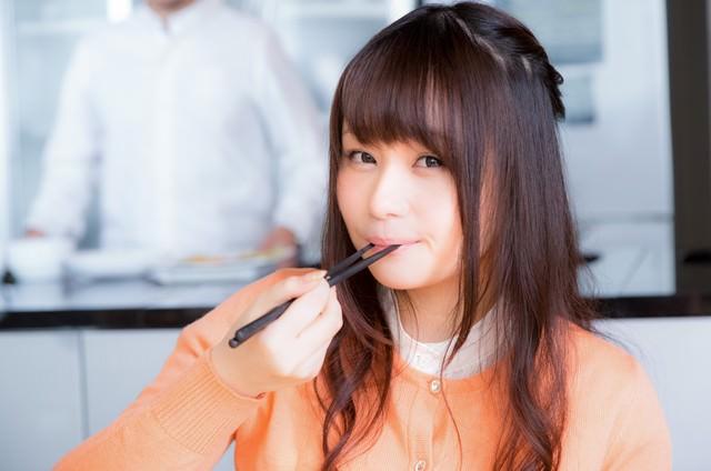 箸が止まらない!絶品料理を口に運ぶ女性の写真