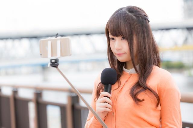自撮り棒(セルカ棒)を使って現場の様子を伝える女子アナの写真
