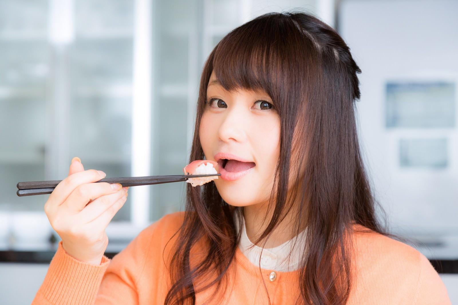 「一口サイズのお寿司を頬張る美女」の写真[モデル:茜さや]