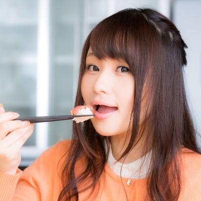「一口サイズのお寿司を頬張る美女」の写真素材