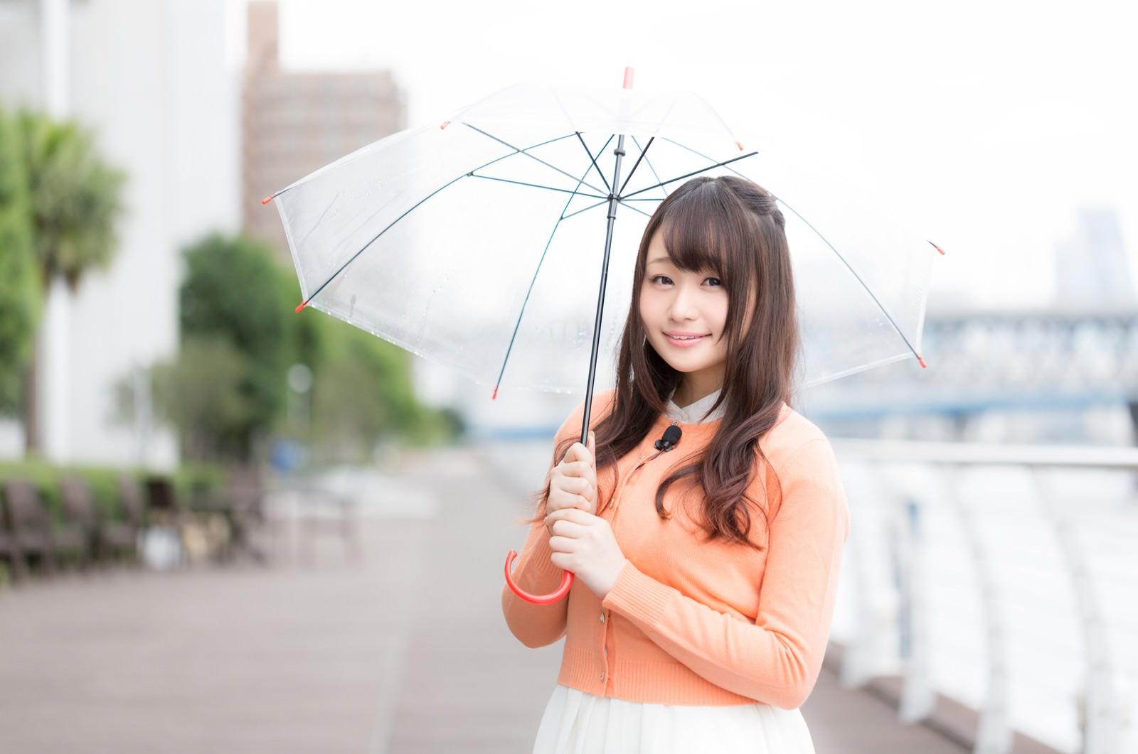「雨の様子を傘をさして伝える美人キャスター雨の様子を傘をさして伝える美人キャスター」のフリー写真素材を拡大