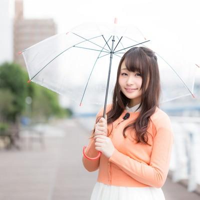 「雨の様子を傘をさして伝える美人キャスター」の写真素材