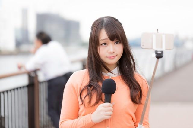 スマホで現地取材を行う女性アナウンサーの写真