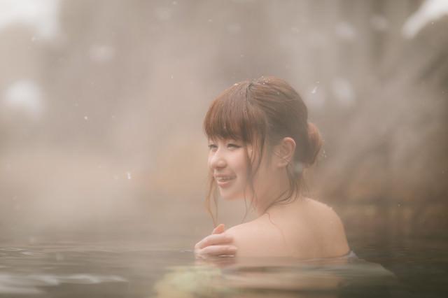 雪見露天風呂で満足そうに顔をほころばせる女性の写真