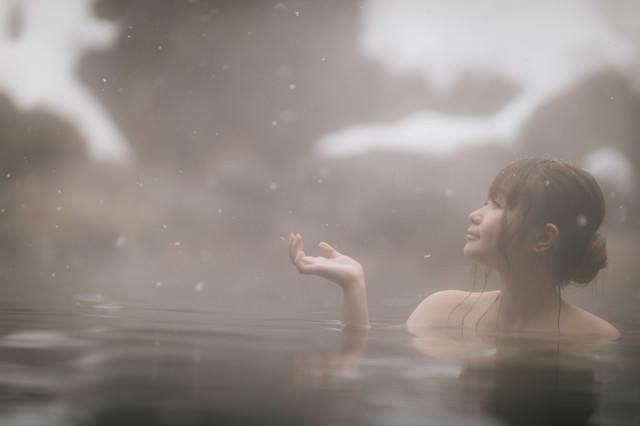 「粉雪舞う露天風呂に浸かる美女」のフリー写真素材