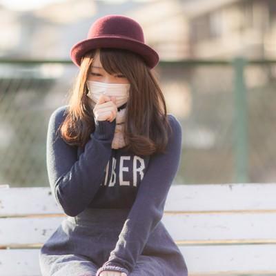 「風邪をひいて咳がツライマスク美女」の写真素材