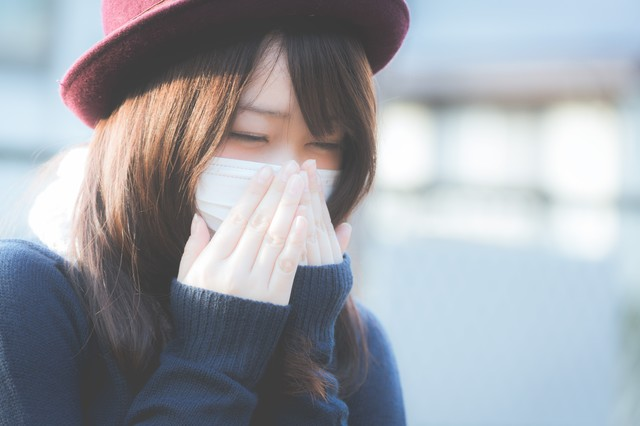花粉症でくしゃみが止まらないマスクをした女性の写真