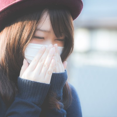 「花粉症でくしゃみが止まらないマスクをした女性」の写真素材