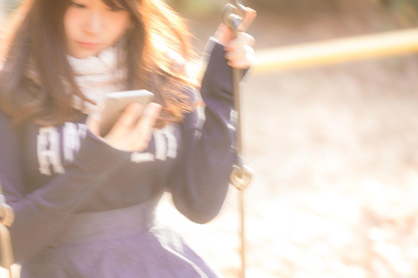 「ブランコに揺られながらスマホを操作する女性」の写真[モデル:茜さや]