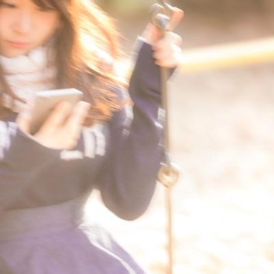 「ブランコに揺られながらスマホを操作する女性」の写真素材
