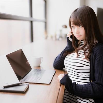 「クライアントへ確認の電話を入れるIT女子」の写真素材