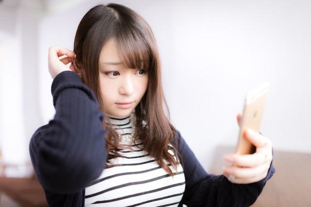 スマホを鏡代わりにする女性モデルの写真