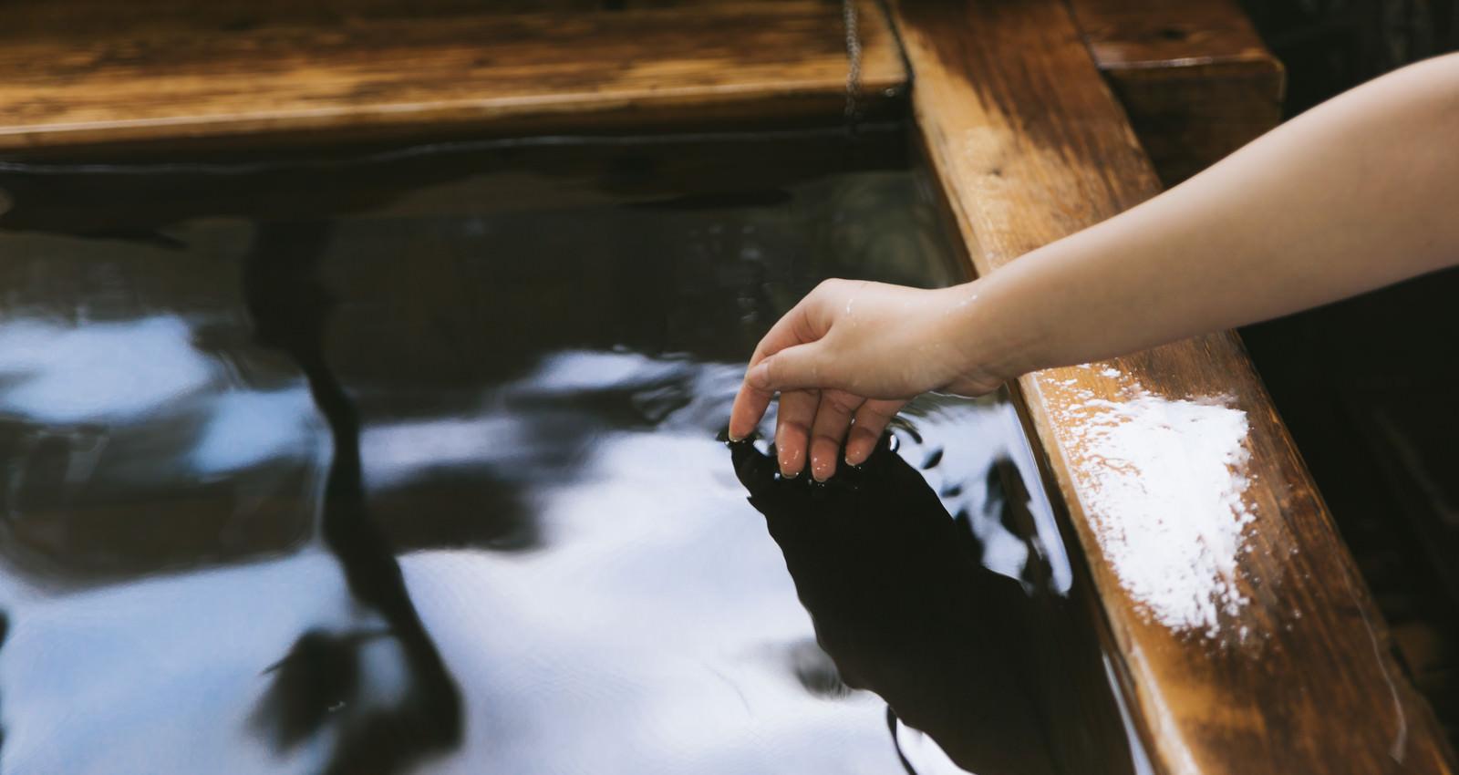 「湯船に手を入れて湯温を確かめる」の写真