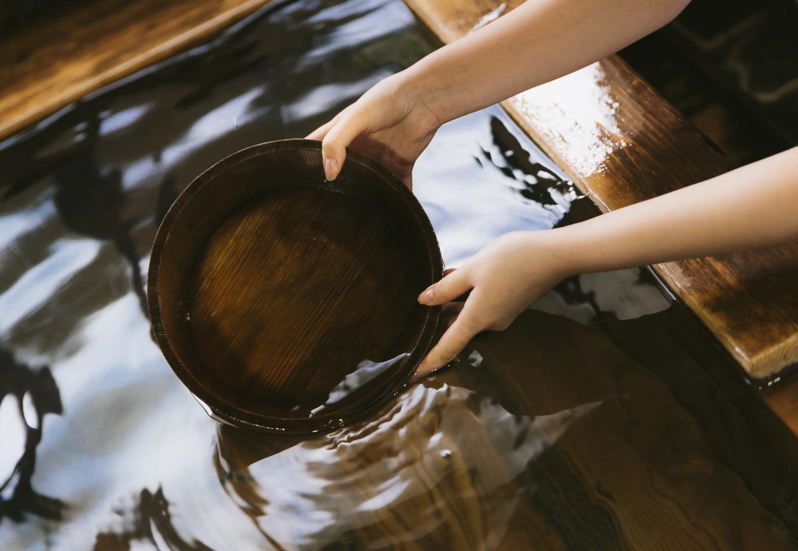 「湯船にかけ湯の桶を入れる」の写真