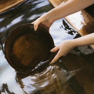 「湯船にかけ湯の桶を入れる」の写真素材