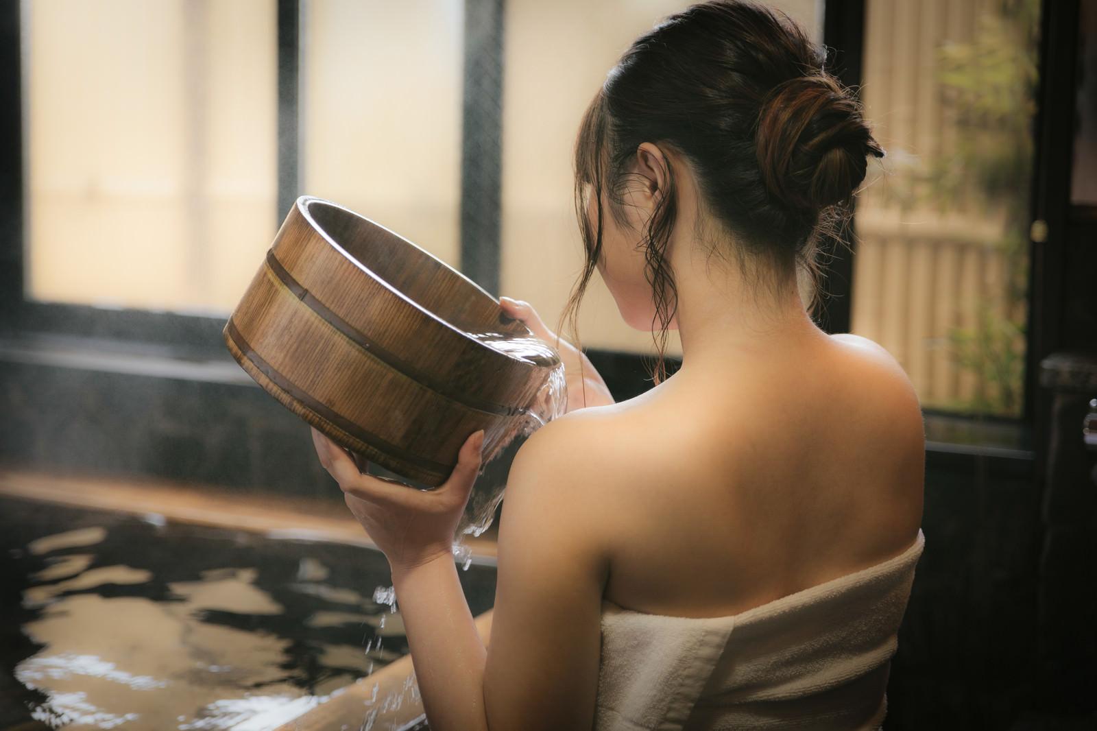 「肩にかけ湯をする女性の後姿」の写真[モデル:茜さや]