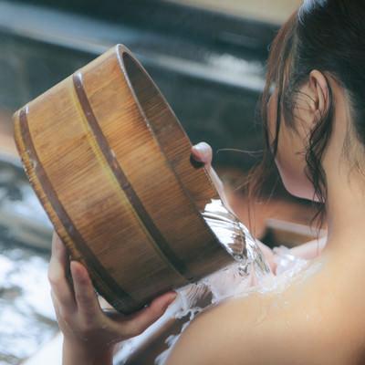 肩にかけ湯する女性の後ろ姿の写真