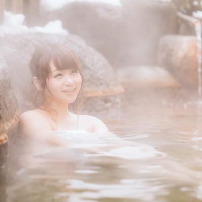 「源泉かけ流しの温泉を楽しむ湯けむり女子」の写真素材