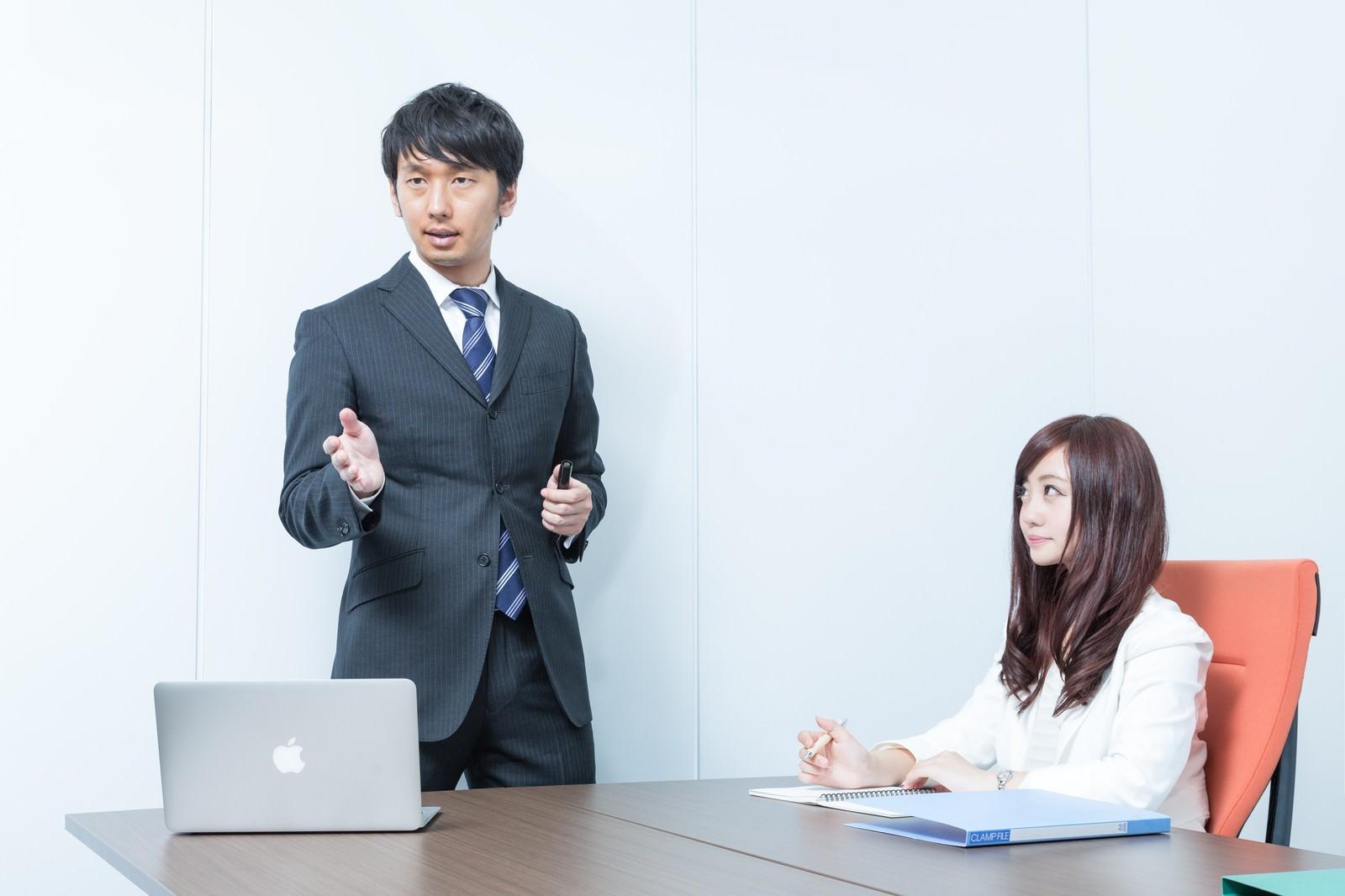 「プレゼン中の上司を見つめる恋するキラキラ広報」の写真[モデル:大川竜弥 河村友歌]
