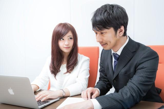 研修中パソコンの画面ではなく先輩の顔を見つめる新入社員の写真