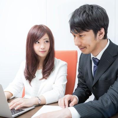 「研修中パソコンの画面ではなく先輩の顔を見つめる新入社員」の写真素材