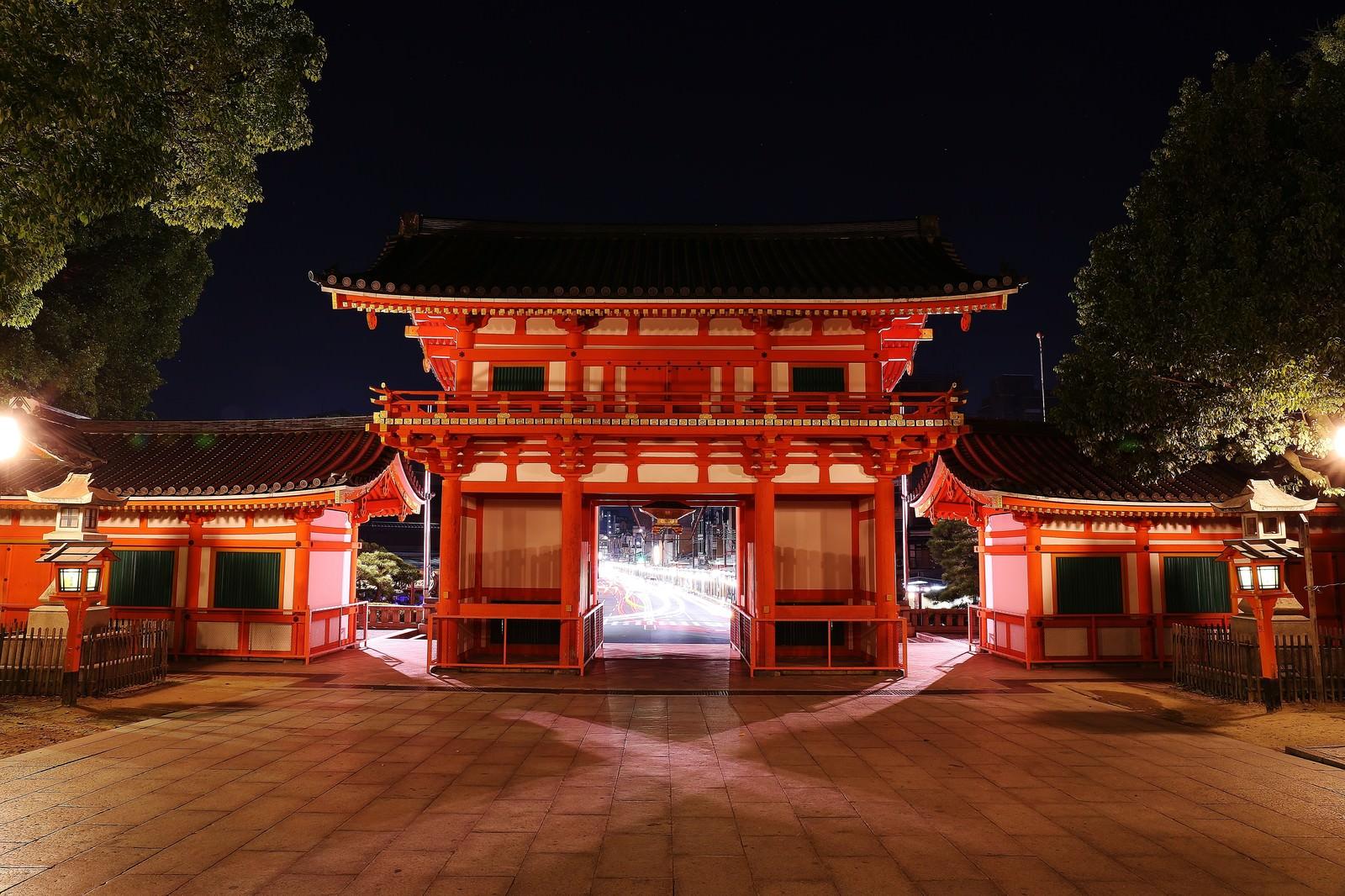 「門から見えるヘッドライトの光跡」の写真