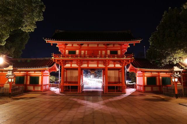 門から見えるヘッドライトの光跡の写真