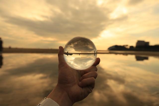 手に持った水晶球で夕暮れ時を写しこむの写真