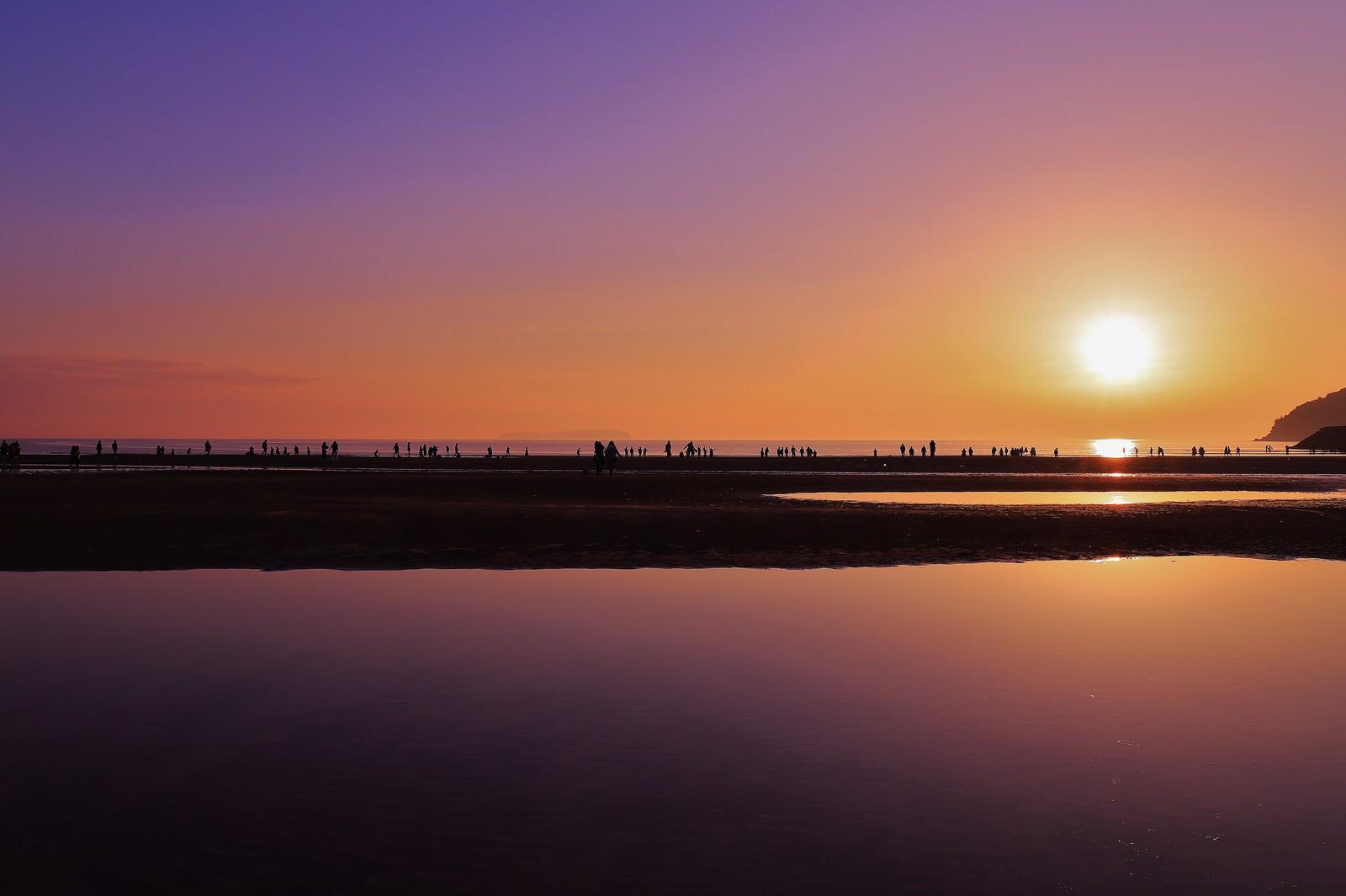 「沈む夕日と浜辺で遊ぶ人々のシルエット」の写真
