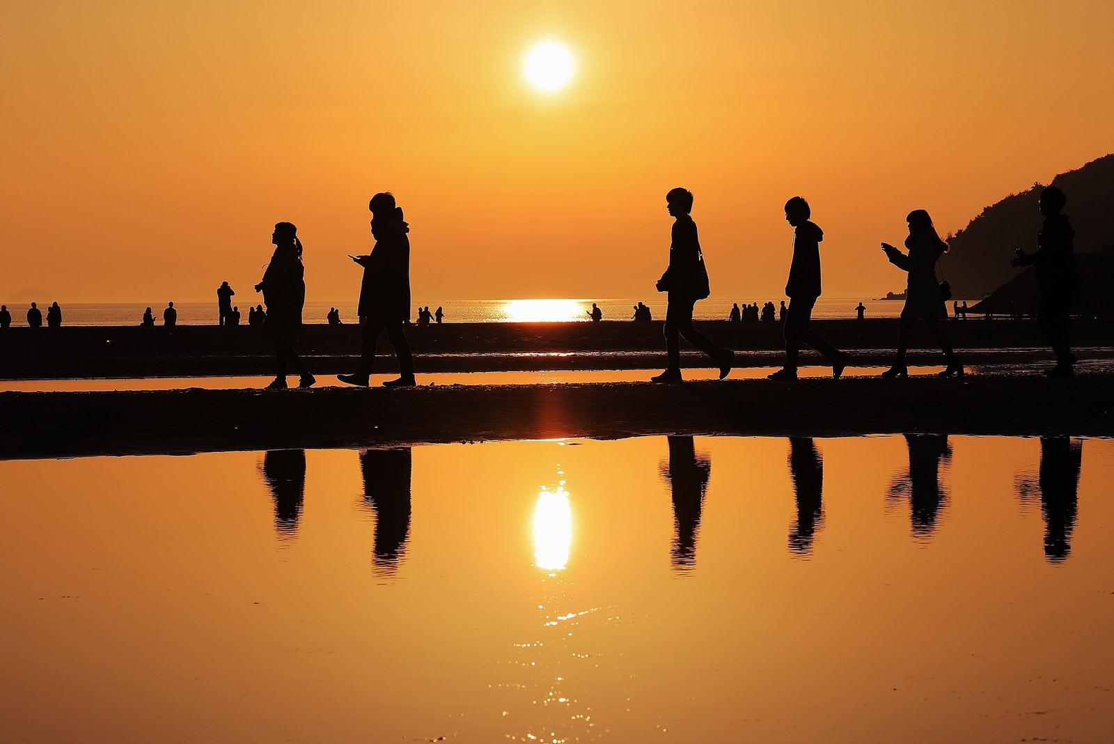 「夕暮れ時に砂浜を散策する人達のシルエット」