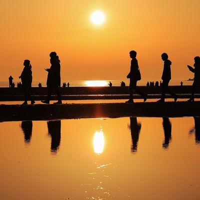 夕暮れ時に砂浜を散策する人達のシルエットの写真