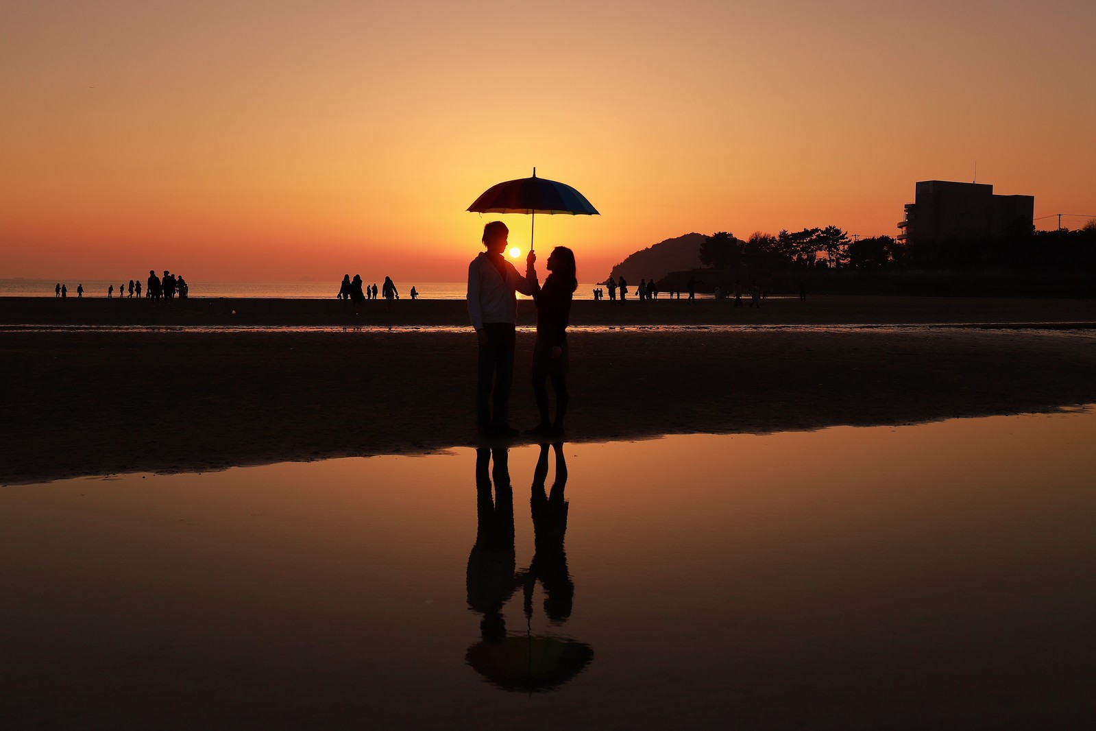 「夕暮れ時に浜辺で相合傘するカップル」