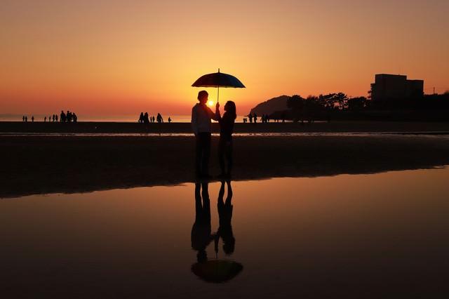 夕暮れ時に浜辺で相合傘するカップルの写真
